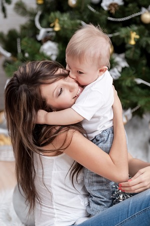 Happy mother with her son by the fireplace under the Christmas tree photo