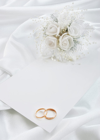The wedding invitation with wedding rings and a bouquet of the bride on a white background Stock Photo