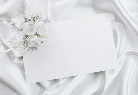Az esküvői meghívó, egy csokor a menyasszony fehér alapon