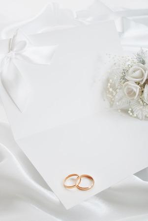 결혼 반지와 결혼식 초대 및 흰색 배경에 신부의 꽃다발