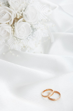 The wedding rings and a bouquet of the bride on a white background