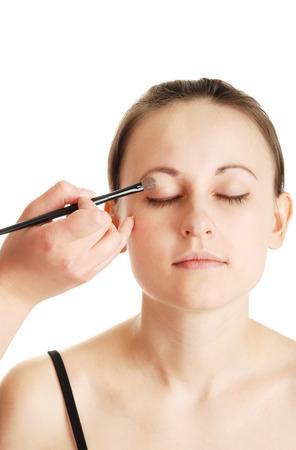 visagiste: visagiste does make-up the young girl