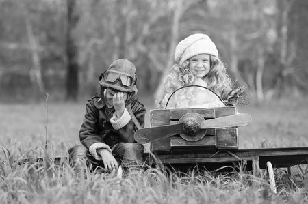 Boy with a girl with a homemade airplane in a field in sunny autumn day