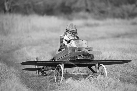 Young female pilot in a homemade plane in a field on a sunny autumn day
