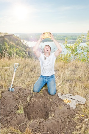 gold shovel: Young man on the edge digs gold hot summer day Stock Photo