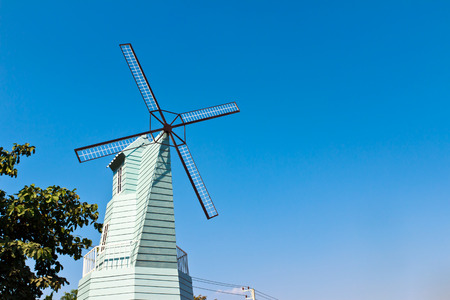 wood windmill with blue sky