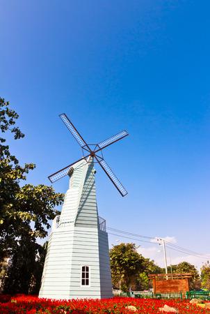 wood windmill in flower garden