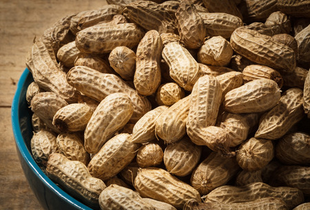 pygmy nuts: groundnut in blue bowl on wood background