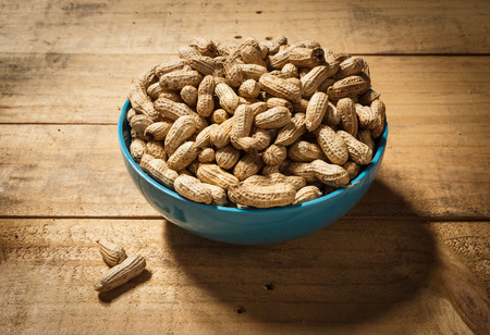 goober peas: groundnut in blue bowl on wood background