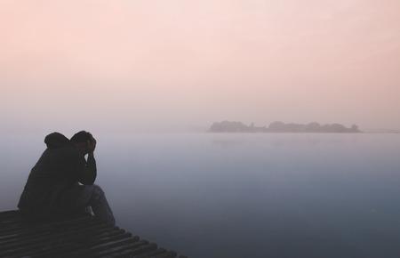 hombre solo: hombre solo se sienta con la emoción de tristeza en el muelle de madera
