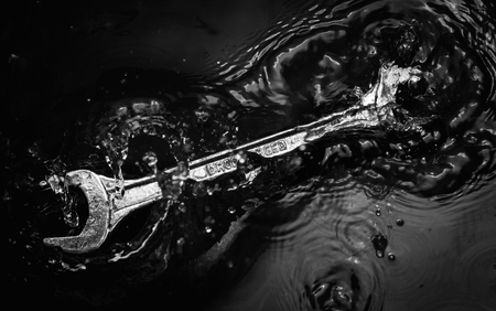 recreate: wrench tool in water splash with low key tone