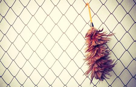 broom handle: duster on metal net background