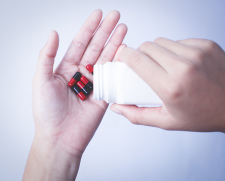 pain killers: hands holding medicine capsule with soft color