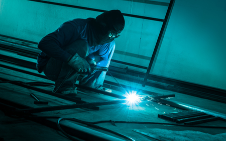 steel making: worker making sparks  from welding steel in dark room