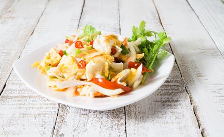 spicy salad with fried eggs. yum kai dao in thai name. thai cuisine on white wood Stok Fotoğraf