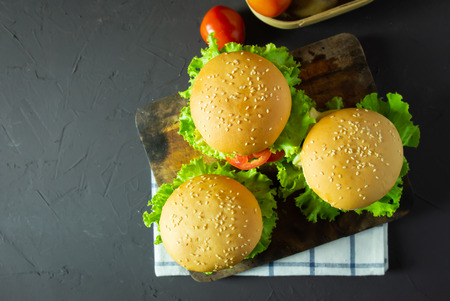 homemade hamburger with pork, onion, tomato, lettuce and cheese on rustic dark background. top view