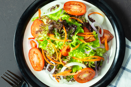 homemade vegetable salad tomato, carrot, onion, spinach, and lettuce on black board. top view Stok Fotoğraf