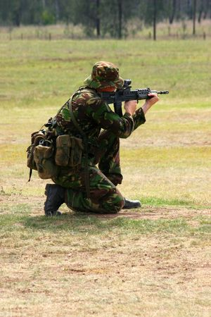 Soldier firing rifle on a range photo