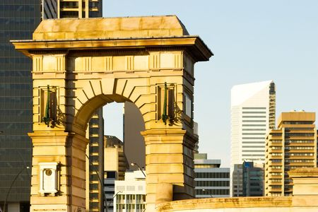 The memorial arch contrasts with the modern buildings behind. Southbank Brisbane, Queensland, Australia Stock Photo
