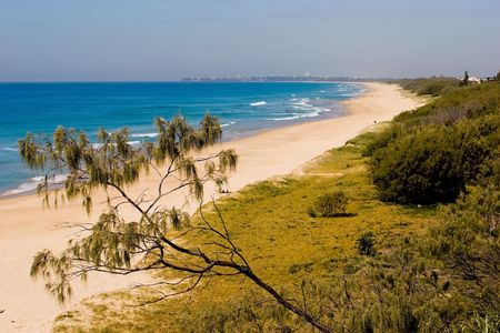 A long sandy beach on the Sunshine Coast of Queensland Australia with the city of Brisbane in the distance