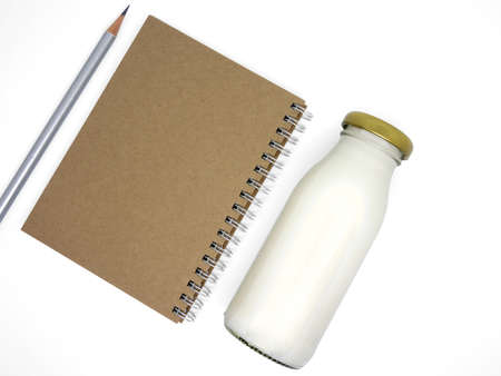 Notebook and milk bottle on isolated white background
