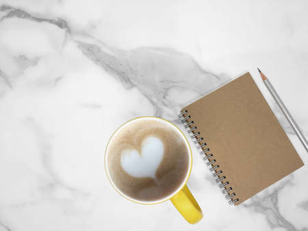 Notebook and coffe cup on marble texture background