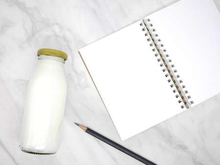 Notebook and milk bottle on marble texture background Standard-Bild