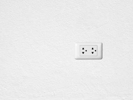 White electric outlet mounted on white wall Standard-Bild