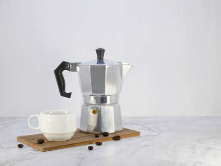 Coffee maker moka pot and a cup on marble  table.