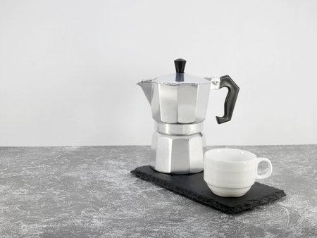 Coffee maker moka pot and a cup on stone background. Standard-Bild