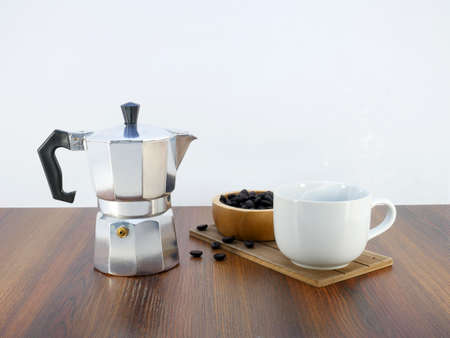Coffee maker moka pot and a cup on wooden table.
