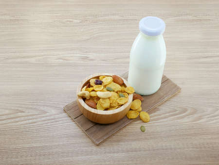 Grains cornflakes in bowl with milk bottle on wooden background.