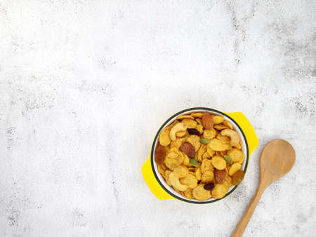 Grains cornflakes in bowl with spoon on white texture background.
