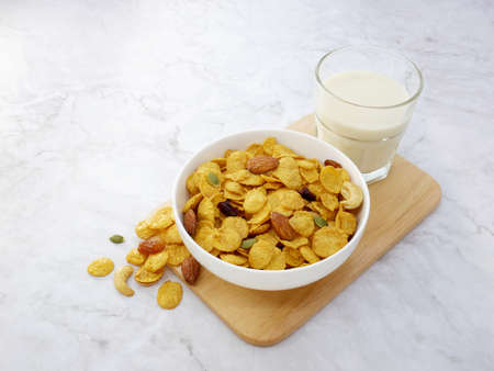 Grains cornflakes in bowl with milk glass on marble background. Standard-Bild