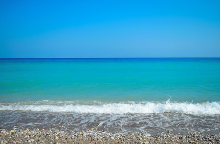 Wave with foam rising sand. Aegean sea