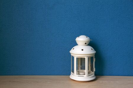 White lamp with blue wallpaper