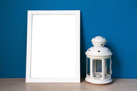 White frame and lamp with blue wallpaper