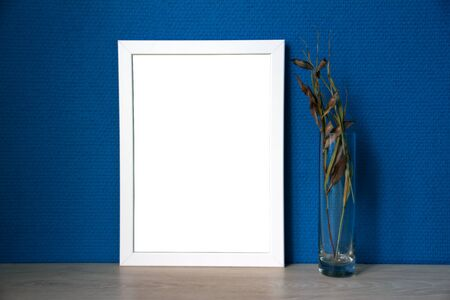 White frame and glass vase with branches with blue wallpaper