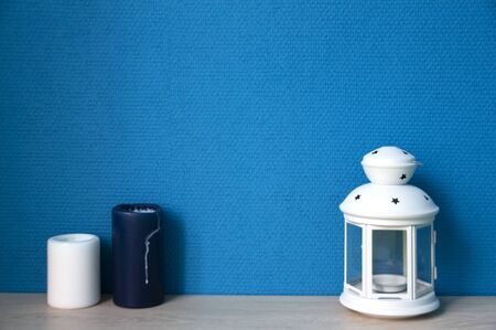 Candles and white lamp with blue wallpaper Imagens