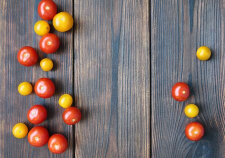 Red and yellow cherry tomatos on dark wooden boards