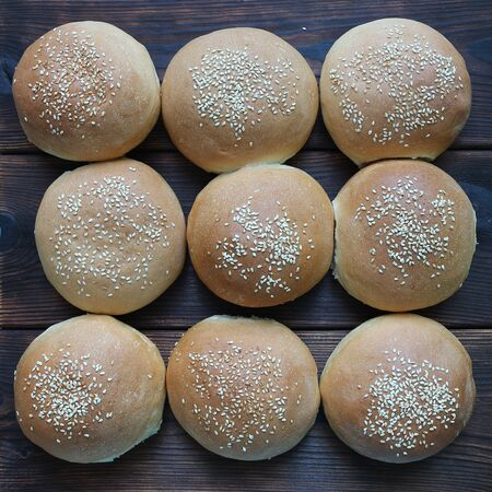Baked buns with sesame on the dark board