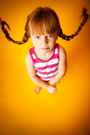 Upset Little Girl with Pigtails, Isolated on Orange Фото со стока
