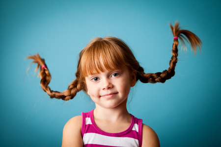 Cute Little Girl with Pigtails, Isolated on Teal