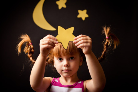Whimsy Little Girl with Pigtails Holding Star at Night Stock Photo