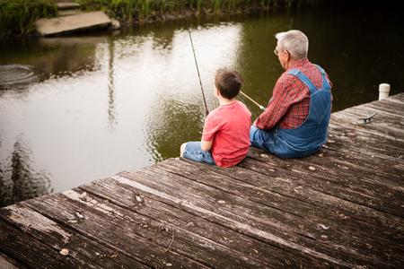 Little Boy Fishing with Great Grandfather on Dock Standard-Bild