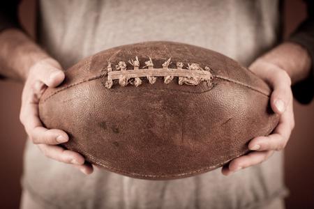 Man Holding Vintage, Well-Used Leather Football