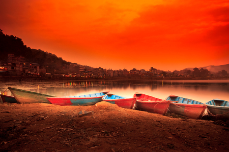 phewa: Sunset View of Phewa lake with colourful boats in Pokhara,Nepal. Stock Photo