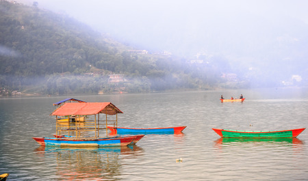 phewa: Foggy morning view of Phewa lake with colourful boats  in Pokhara,Nepal.