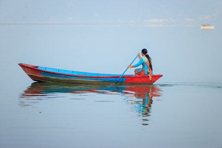 phewa: Pokhara,Nepal- Dec 11,2015:A beautiful woman is sailing a boat in phewa  Lake to run her day to day life. Editorial