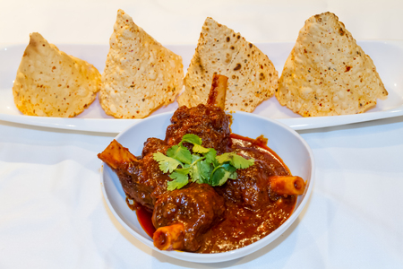 rajasthani: Rajasthani Style mutton curry and dried stylish papad on the Table.